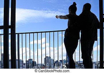 Young couple looks at urban city skyline cityscape view