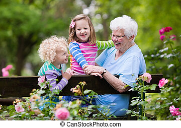 Grandmother and kids sitting in rose garden - Happy senior...