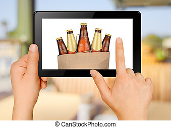 Ordering beer via internet - Hands holding tablet PC and...