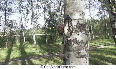 The beautiful woman with a smile looks out from birch and...