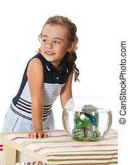 Girl is watching fish in an aquarium