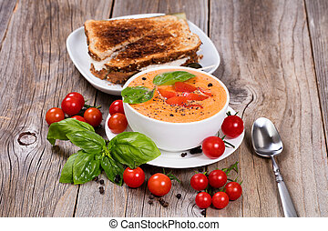 Fresh bowl of creamy tomato soup and sandwich with basil...