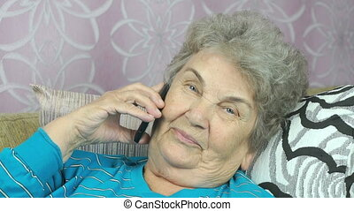 Old woman talking with daughter on mobile phone indoors