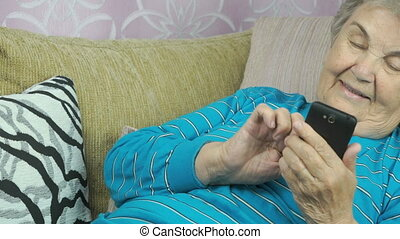 Old woman lying on a beige sofa holds a cellphone