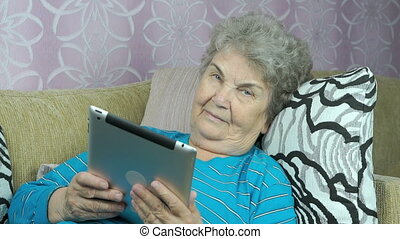 Aged woman holds a tablet computer indoors