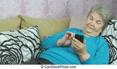 Elderly woman using a mobile phone indoors