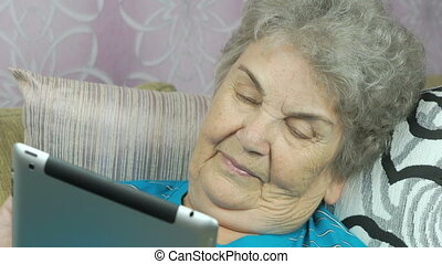 Aged woman holds a tablet computer indoors - Aged woman...