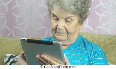 Grandmother uses the new computer tablet at home