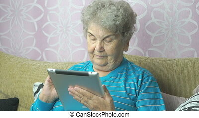 Old woman using a computer tablet