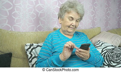 Old lady using a mobile phone sits on a beige sofa at hotel...