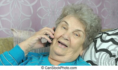 Aged woman talking with daughter on cellphone indoors