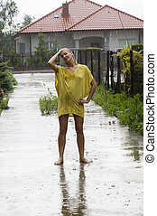 woman under rain - blond woman wearing a yellow dress just...