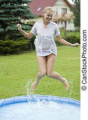 jumping girl - cute blond woman jumping inside a little...