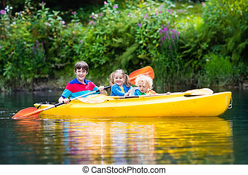 Kids kayaking on a river - Happy family with three kids...
