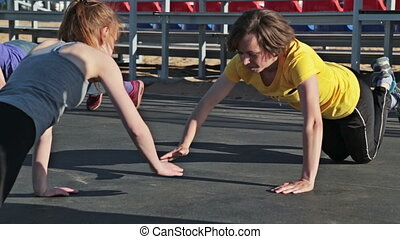 Two young women doing push-ups and clapping hands