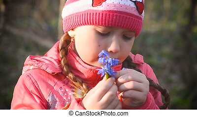 Girl sniffing blue snowdrops - Girl in spring forest blue...