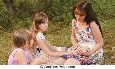 Children with mother pet a puppy