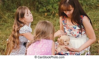 Children with mother iron a puppy