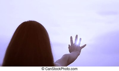 The girl pulls a hand to the sun