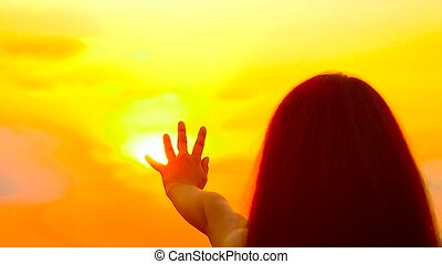 The girl pulls a hand to the gold sun, in the beautiful sky