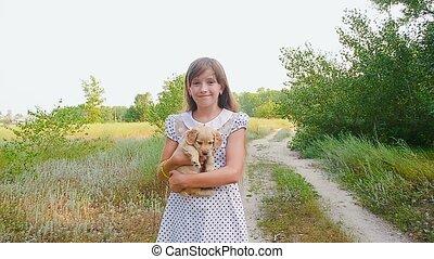 Girl carries a little puppy