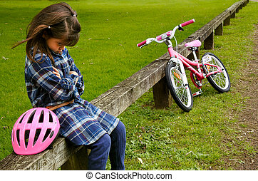 Sad little girl do not know how to ride a bike. Children and...