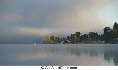 Sunrise over misty lake