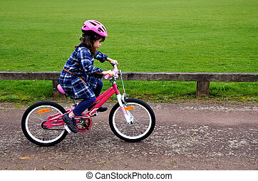 Happy little girl learns how to ride a bike - Happy little...