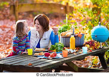 Mother and daughter set table for picnic in autumn - Happy...