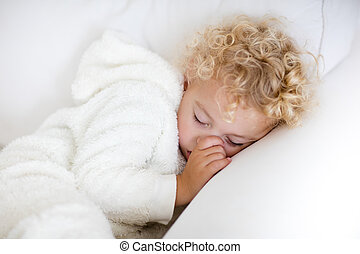 Little boy sleeping on white couch - Cute blond curly little...