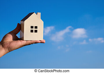 hand holding a house model and a blue sky at background
