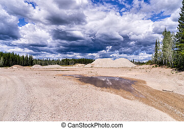 Rain clouds over road sand storage pit