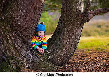Little boy playing in autumn park - Little boy hiding behind...