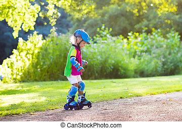 Kids roller skating in summer park - Little girl learning to...