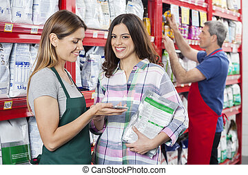Customer Making Payment To Saleswoman In Pet Shop - Portrait...