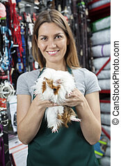 Happy Saleswoman Holding Guinea Pig At Store - Portrait of...