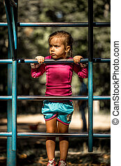 beautiful little girl playing on children's sports trainers...