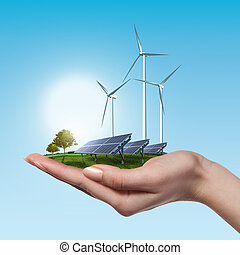 Wind turbines and solar panels in female hand - Wind...