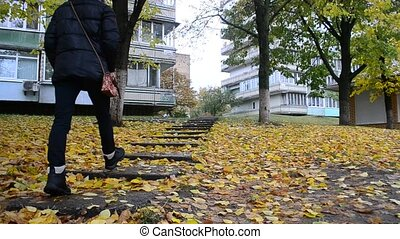 Girl in black clothes and boots walks on footway in autumn -...
