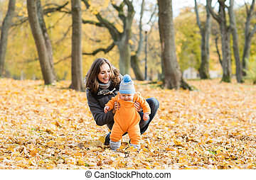 Mother teaching her toddler son to walk in the park. Autumn...