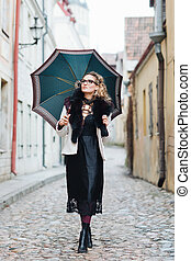 Attractive, stylish woman walking with an umbrella in the...