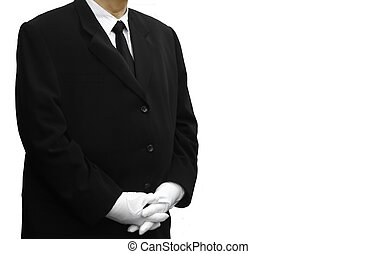 man in black suit standing over white