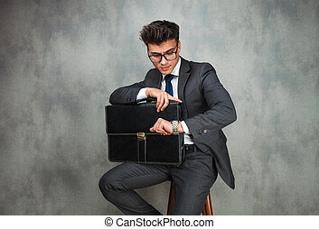 seated young business man holding briefcase is checking time...