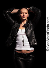 sexy young woman in leather jacket and pants posing