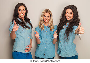 three happy women in jeans clothes making the ok sign