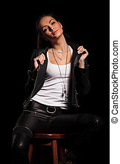 woman in leather clothes is pulling her collar and sits