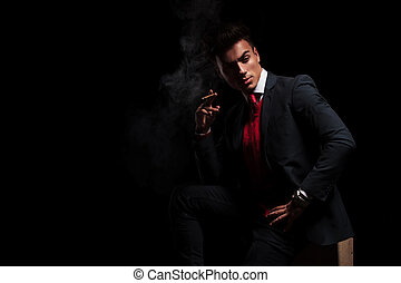 side view of an elegant young businessman smoking a...