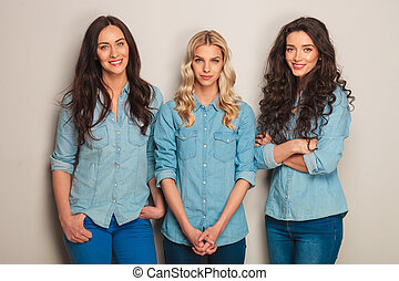 group of three casual women in jeans clothes standin in...