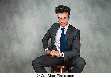 young seated business man checking time on his watch in...