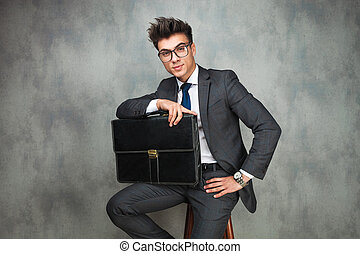 relaxed business man holding a suitcase is sitting